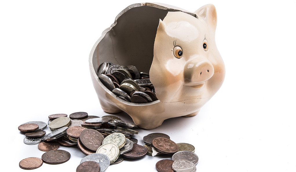 A broken piggy bank with coins falling out.