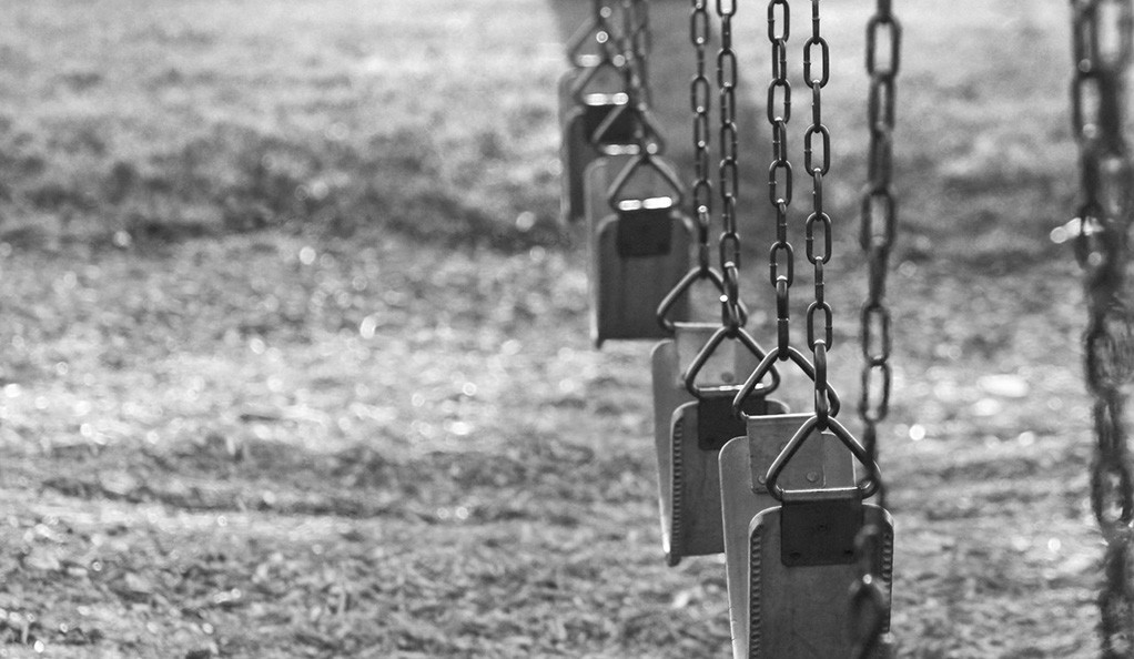 A black and white photo of an empty swing set.