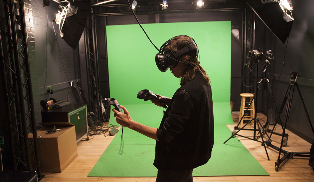 A young woman wearing a virtual reality headset in front of a green screen.