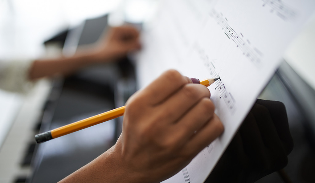 A closeup of a young female composer writing sheet music at the piano.