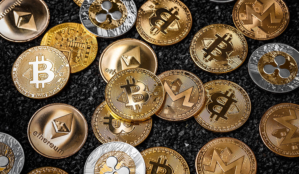 A stack of cryptocurrencies like Bitcoin and Ethereum represented as gold coins.
