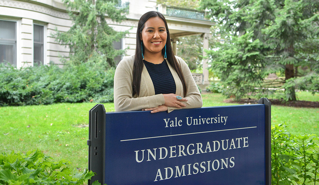 Dinée Dorame stands behind the sign for the Office of Undergraduate Admissions.