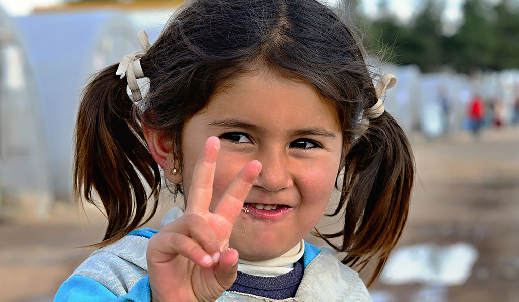 Syrian girl holding up peace sign in a Turkish refugee camp.