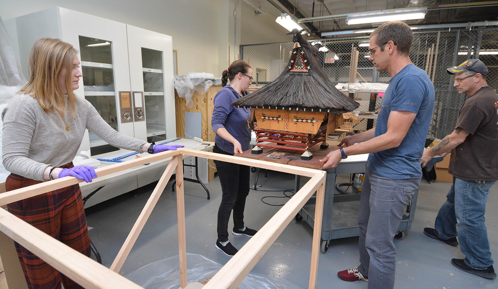 Conservation fellow Aliza Taft and museum assistant Nate Utrup place a model clubhouse from Sumatra into a wooden frame.