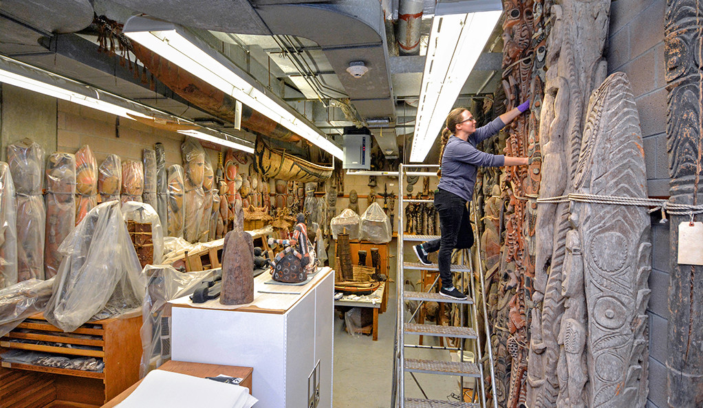 Conservation fellow Aliza Taft inspects ornately carved wooden poles in KGL 27, a sub-basement in the Kline Biology Laboratory