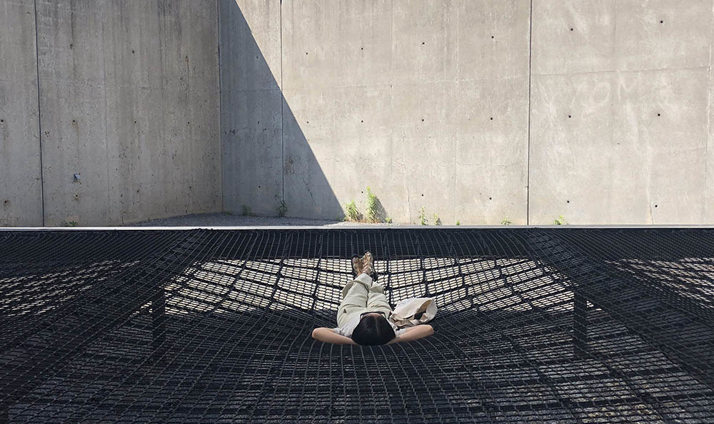 "A person laying in a hammock as part of the installation ""Hide & Seek"" by Jennifer Newsom and Tom Carruthers"
