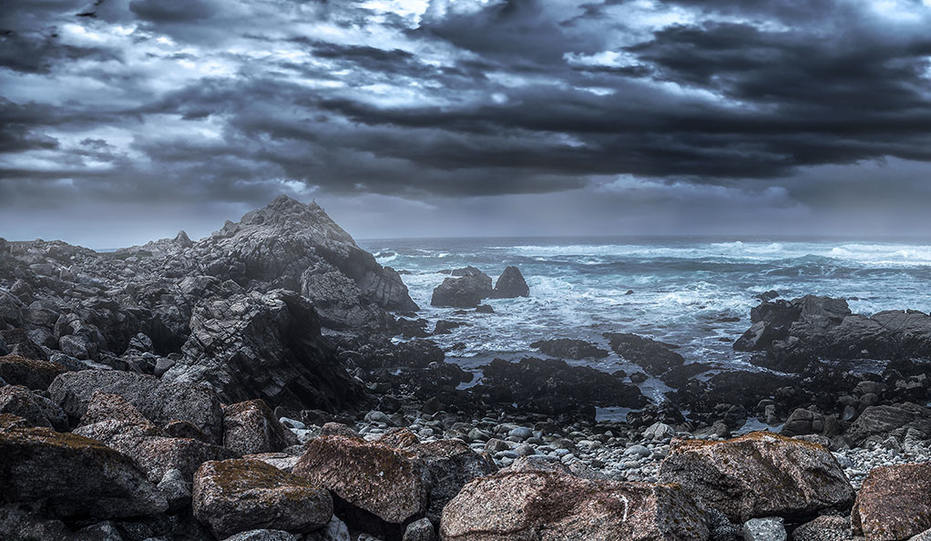 A stormy California beach, with ominous clouds and crashing waves.