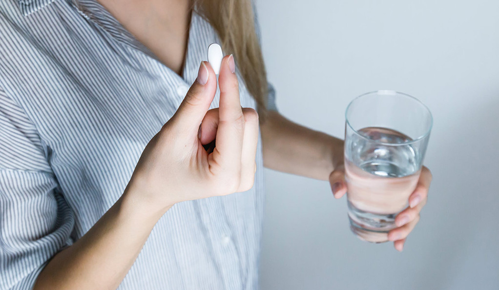 A woman holding a pill and a glass of water.
