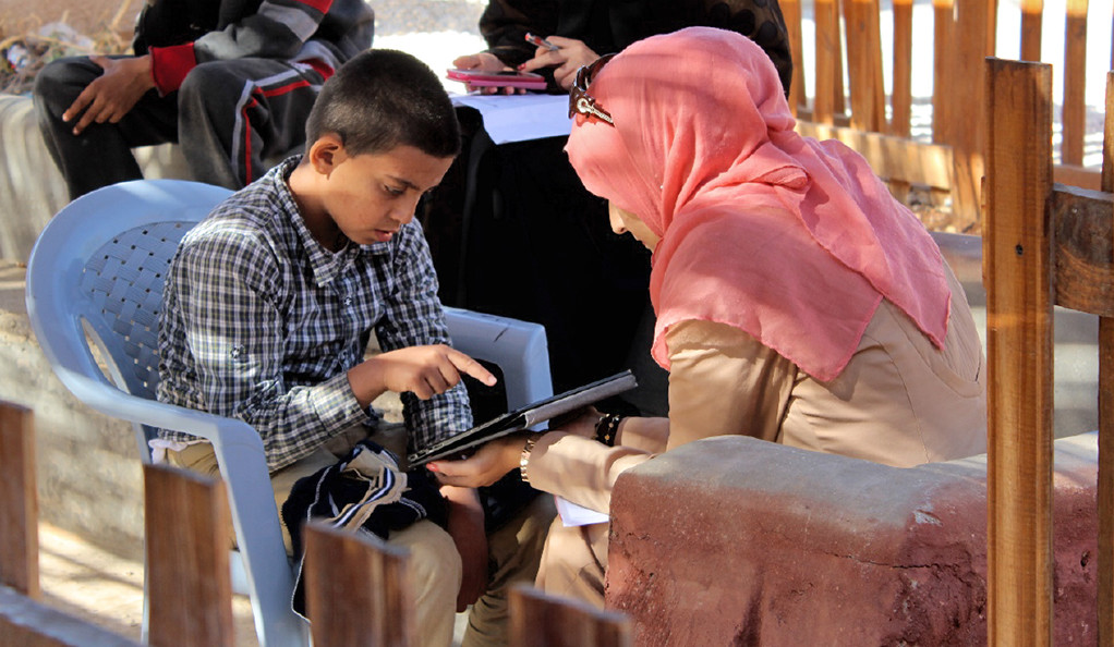 A young Syrian refugee performs tests with a researcher