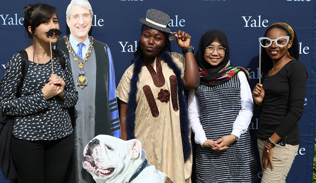 Students post during a Yale Founders Day celebration, with fun props and carboard cutouts of President Salovey and Handsome Dan.