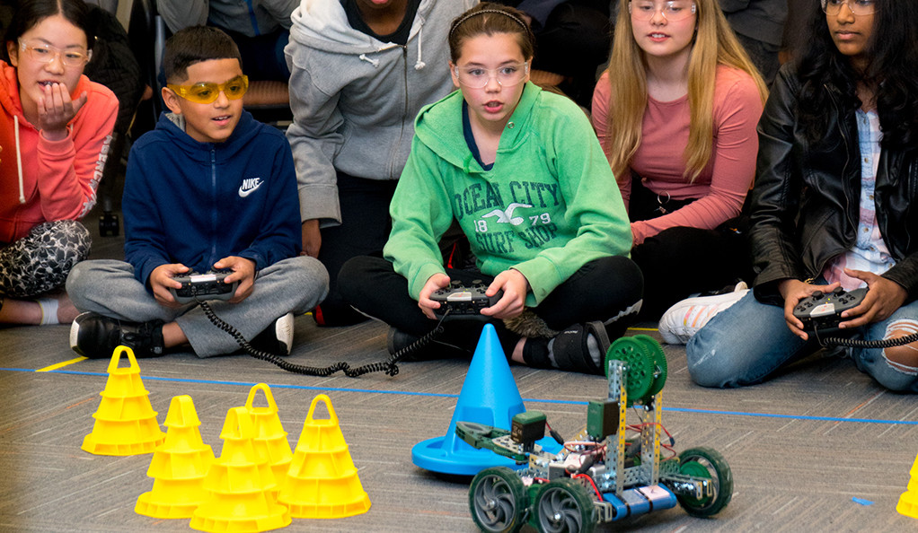 Students watching a robot stack cones during a youth engineering competition.