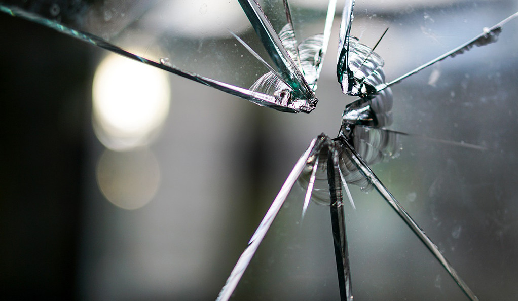 A close-up photo of a pane of glass with a bullet hole in it.