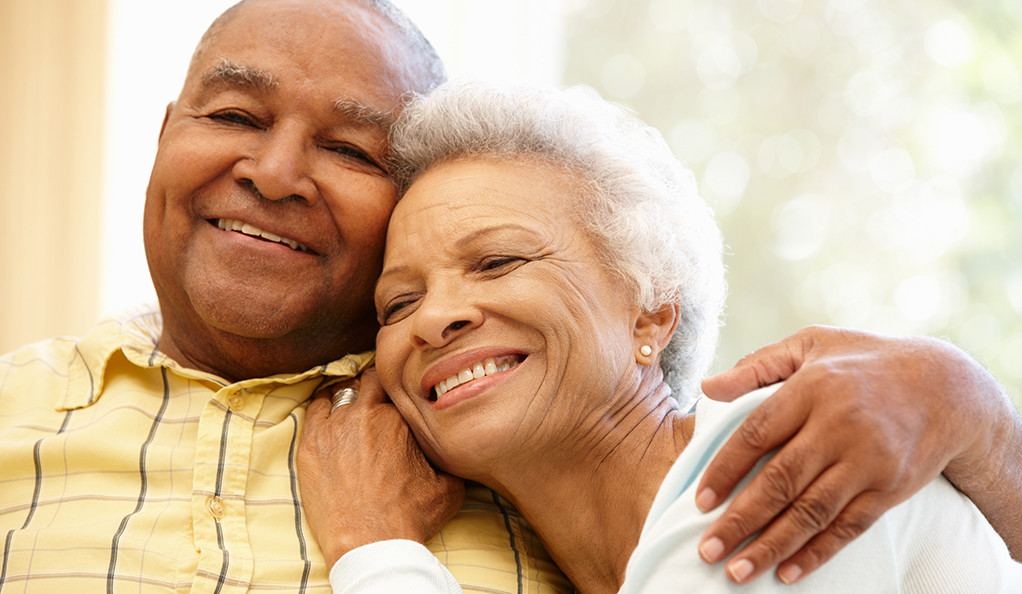 An elderly African American married couple embracing and smiling.