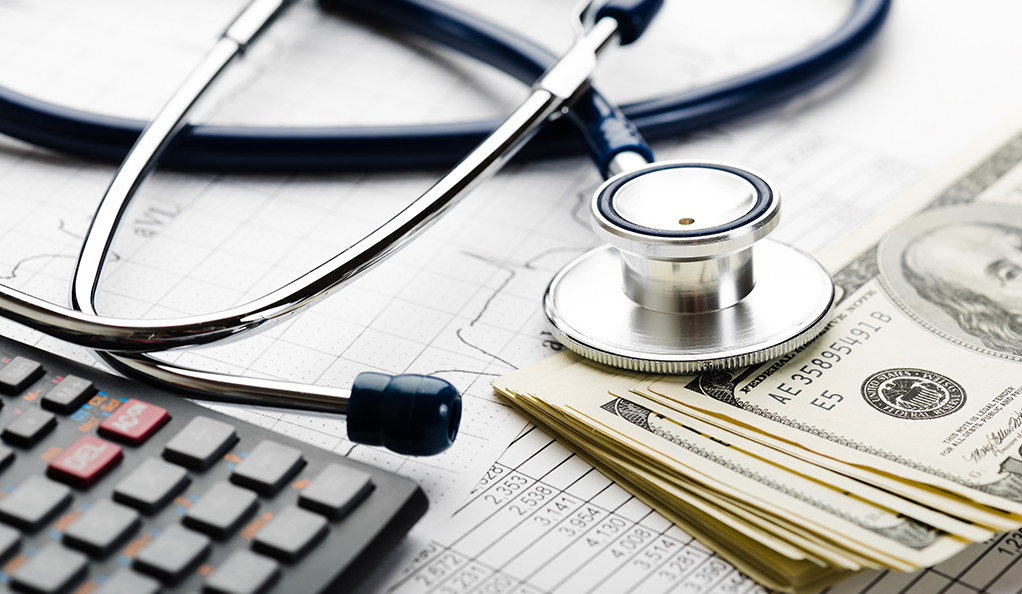 A stethoscope, calculator, and stack of money arranged on top of medical insurance documents.