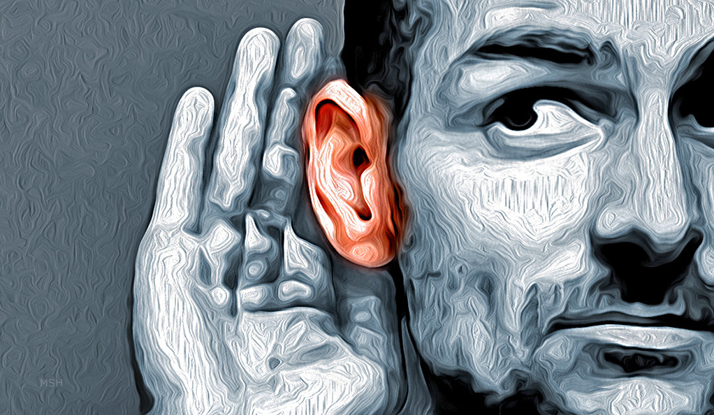 A stock image of a man with his hand positioned behind his right ear.