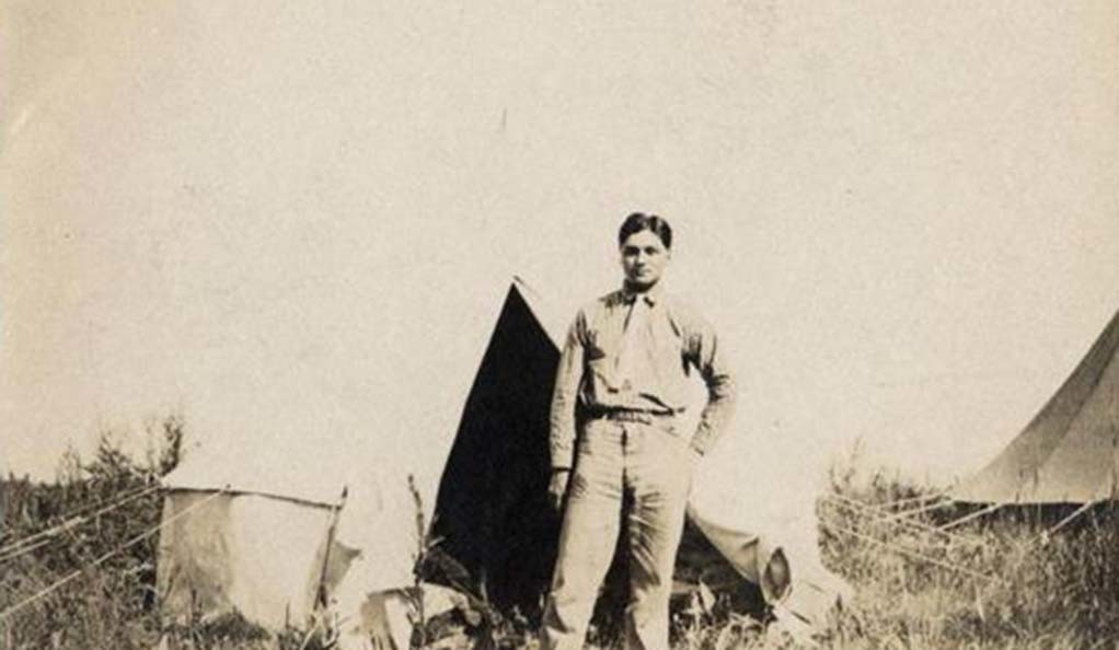A young Henry Roe Cloud poses in front of a tent.