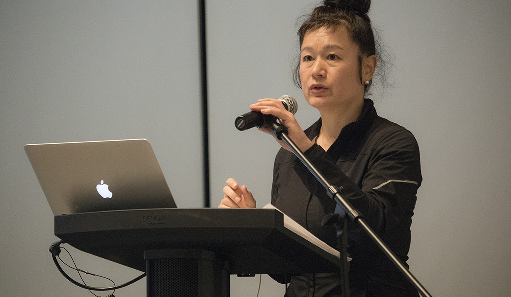 Hito Steyerl lecturing with a laptop and microphone
