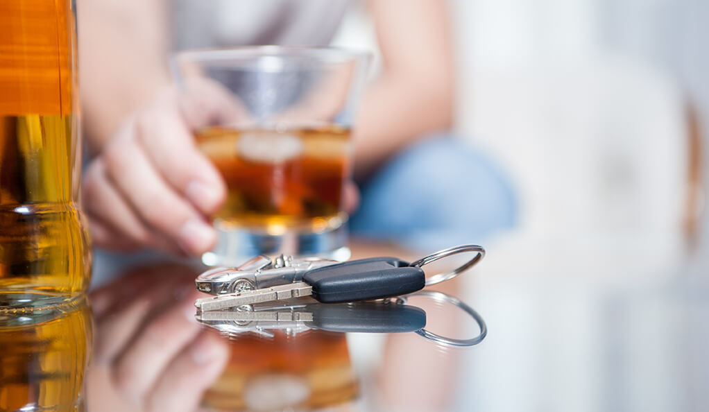 A person holding a glass of liquor and reaching for car keys.