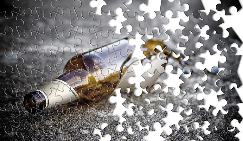 A half-completed jigsaw puzzle depicting a beer bottle on its side.