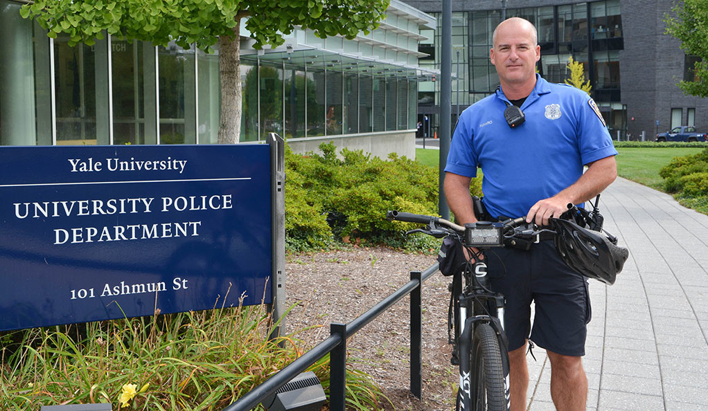 Yale police officer Joe Funaro poses with his bike in front of the Yale Police station.