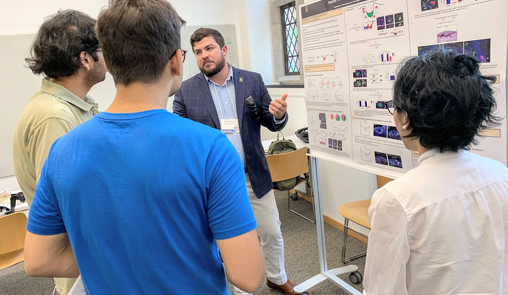 Former Green Beret Justin Jensen explains his research project during a poster session.
