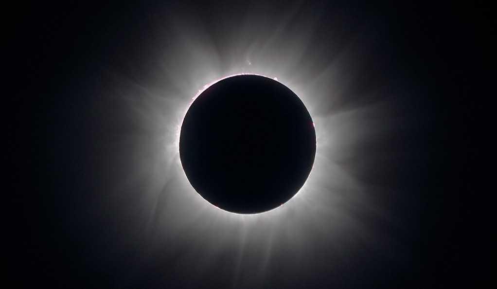 The sun's corona shines behind the moon