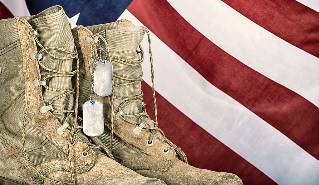 A photo of a soldier's boots in front of the American flag.