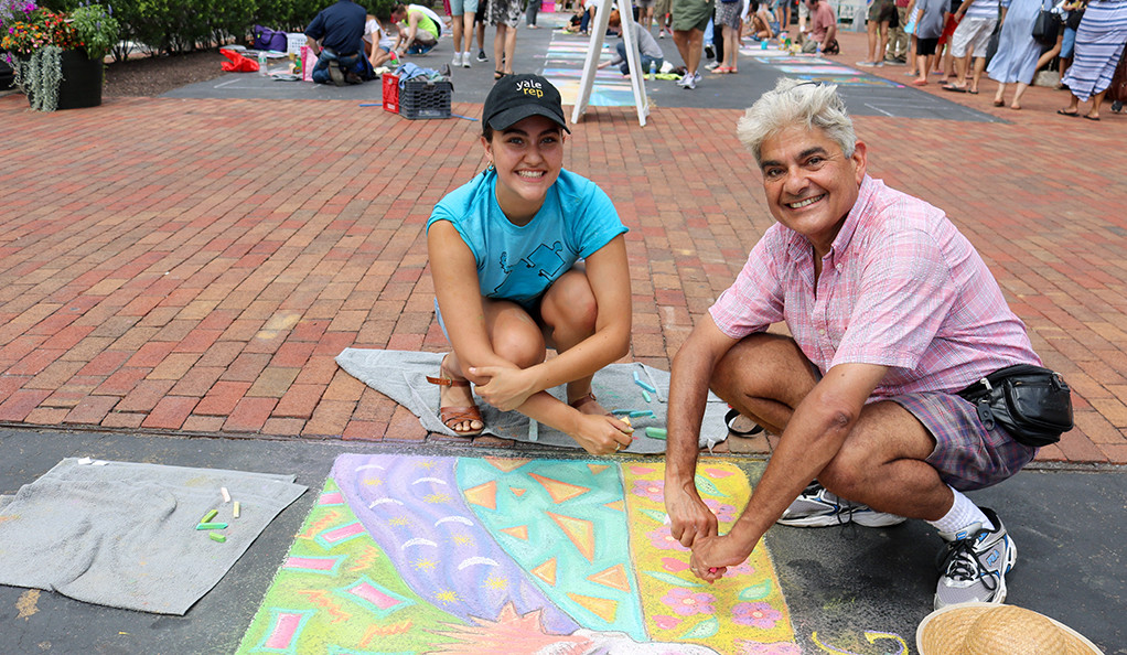 A man and a young girl displaying chalk art on a sidewalk.