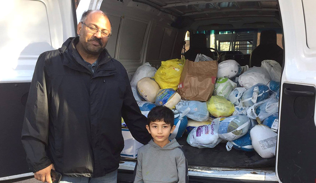 A father and young son strand in front of a van holding donated turkeys.