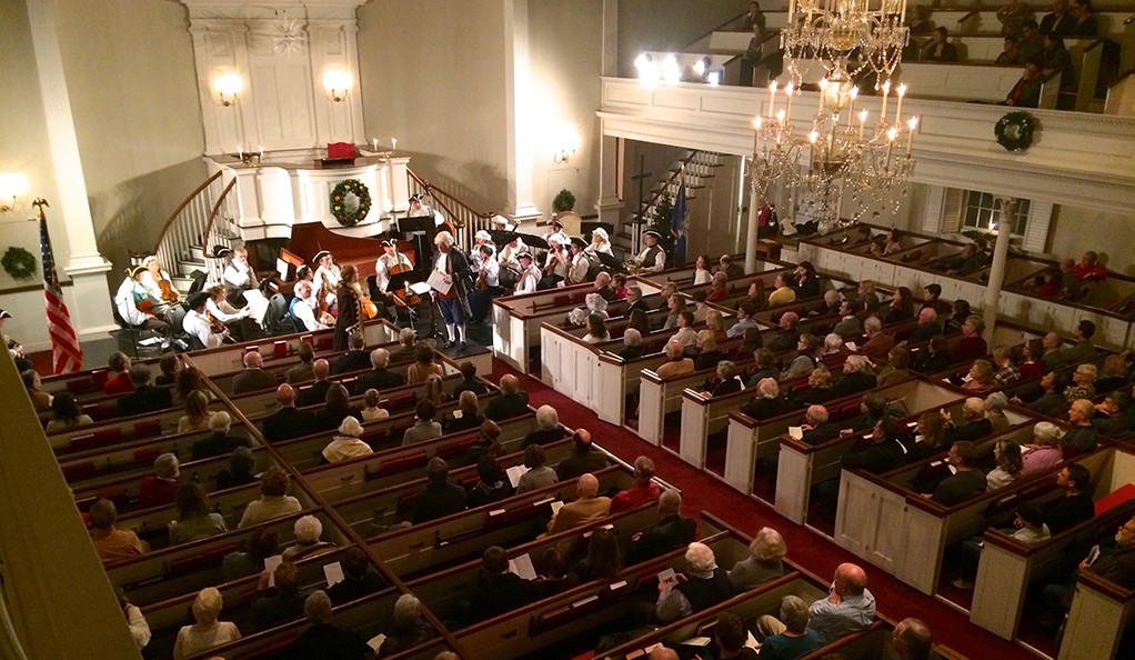 Photo of Orchestra New England, in 18th-century finery, performing a concert.