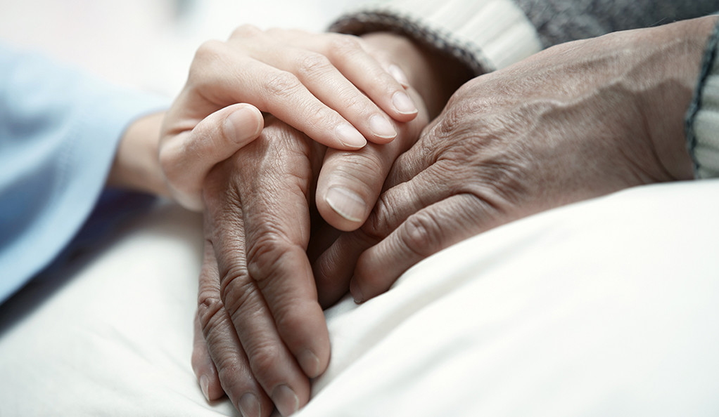 A female hand touching a patient's clasped hands in a gesture of support.