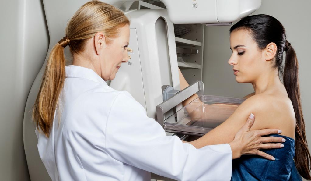 A woman receiving a mammogram.