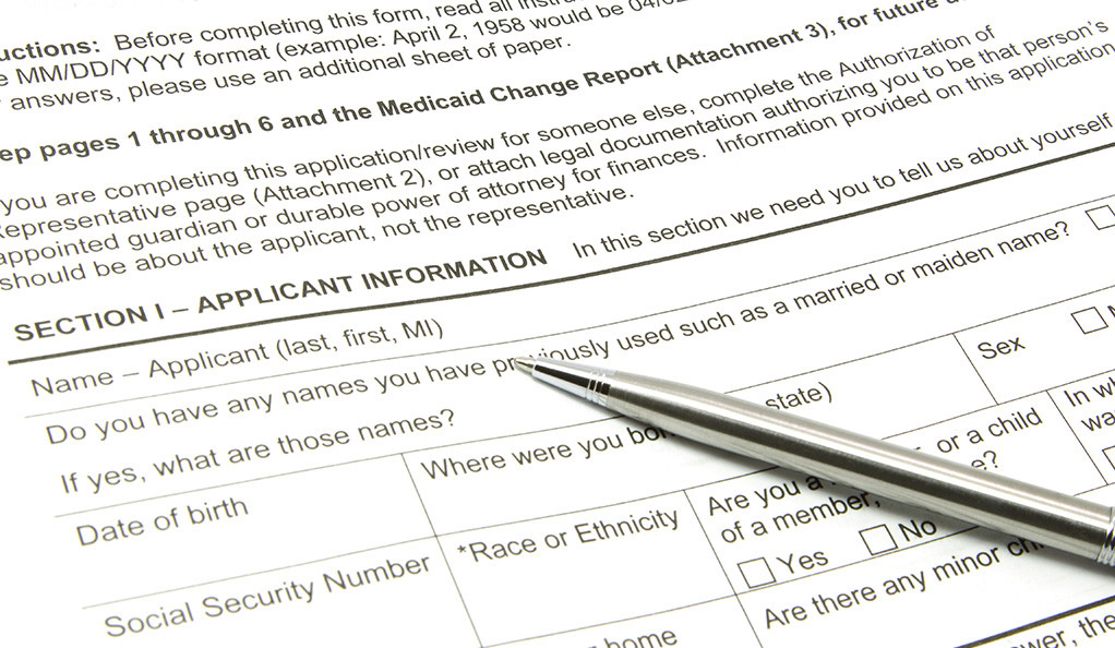A Medicaid application with a silver pen on top.