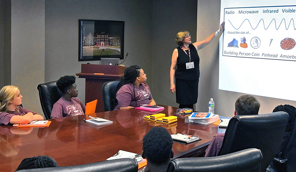 A woman pointing to a scientific diagram on a projector screen while a group of teenagers watch.