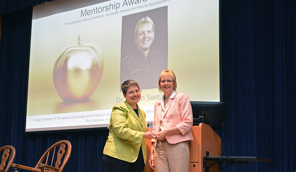 Two women stand before a screen featuring an image of the Postdoctoral Mentoring Prize winner.