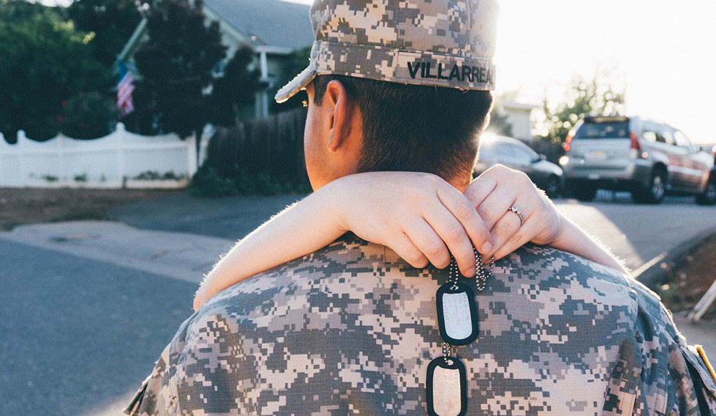 A man in an Army uniform getting a hug from a loved one.