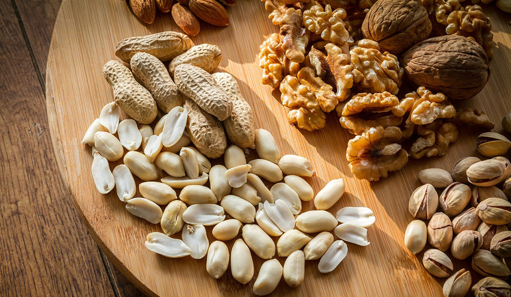 Different varieties of nuts on a wooden board.