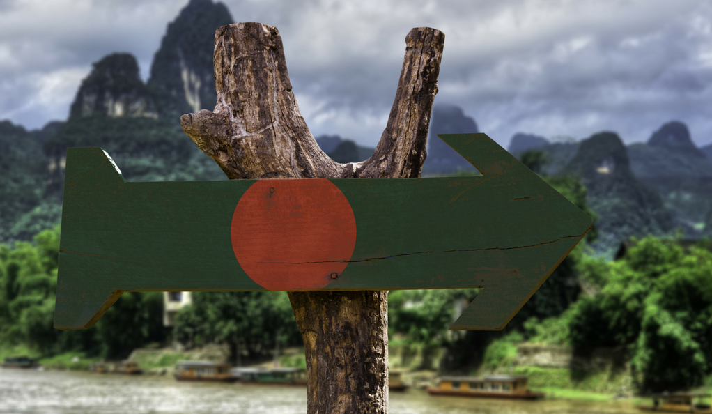 A wooden sign with the Bangladeshi flag painted on, with a forest in the background.