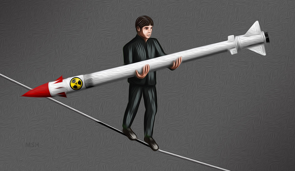 Image of man walking a tightrope balancing a nuclear bomb.