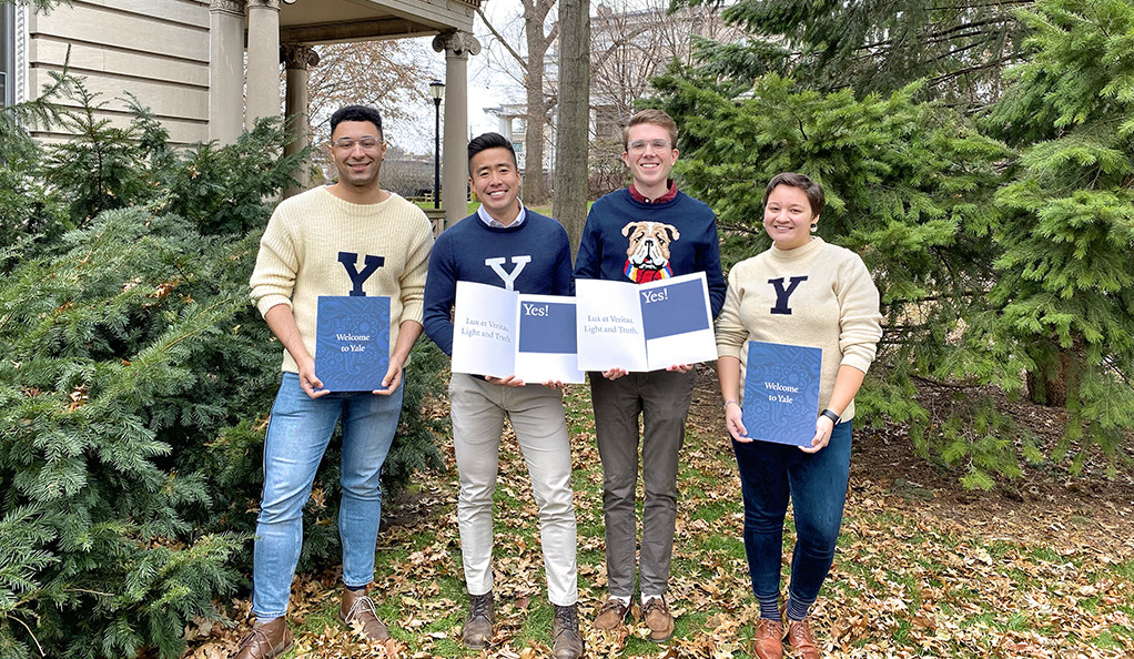 Undergraduate admissions officers pose with welcome packets for newly admitted students