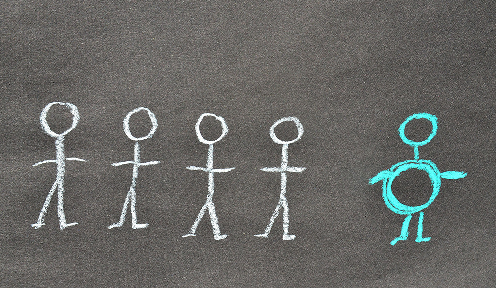 Four stick figures and one highlighted overweight stick figure drawn on a blackboard.