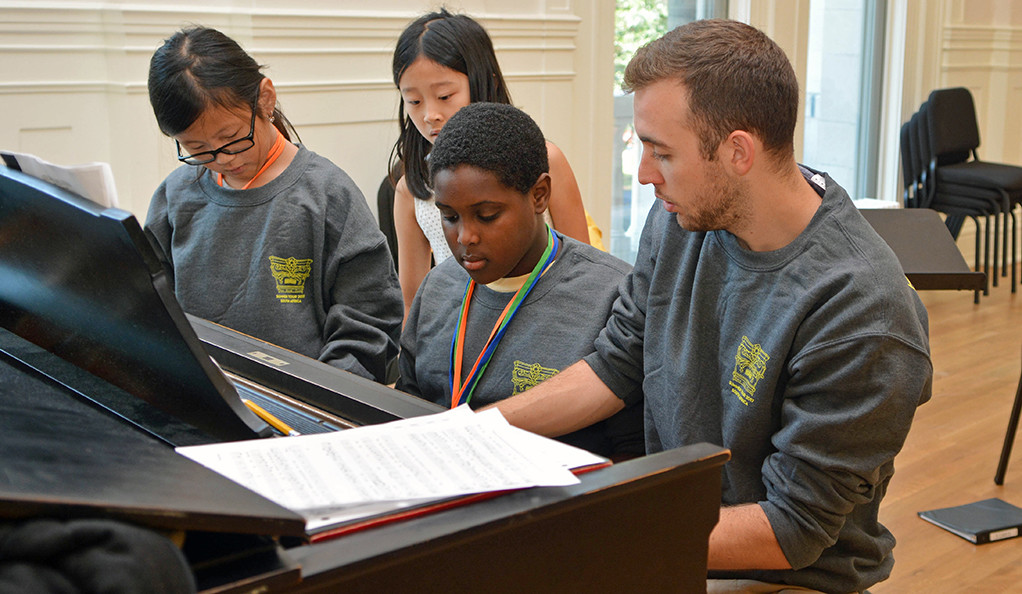 Students and instructor at a piano.