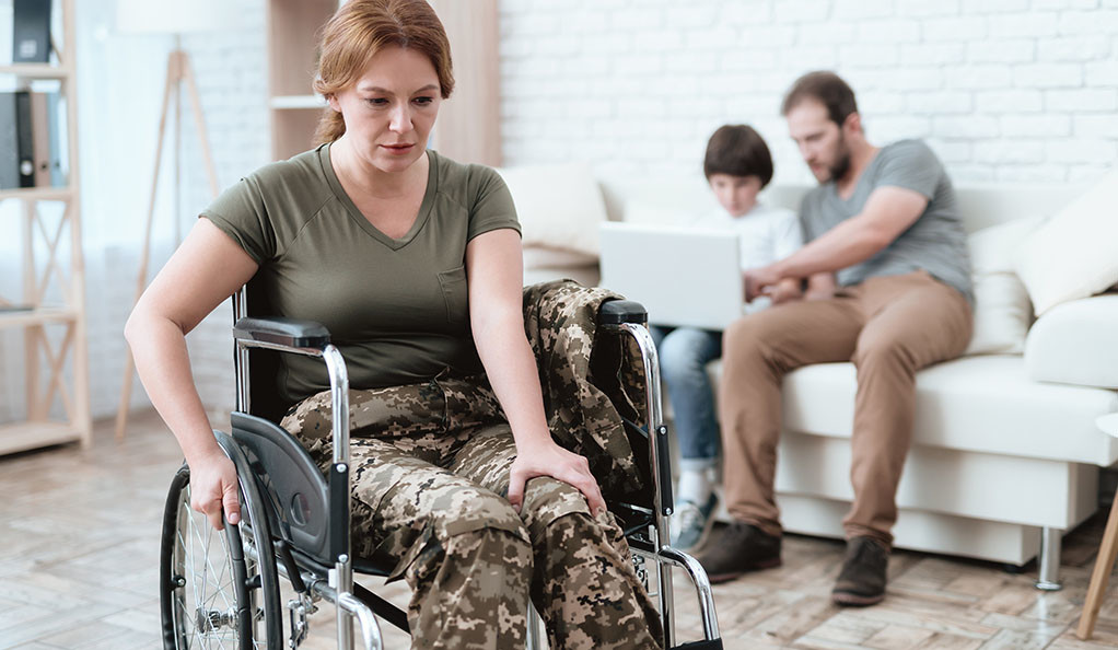 Woman veteran in wheelchair returned from the Army. She's in a military uniform and looks far away or in pain.