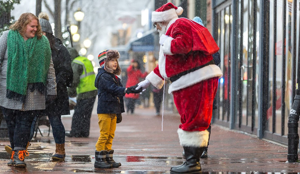 Santa shakes a young boy's hand on Broadway in New Haven.