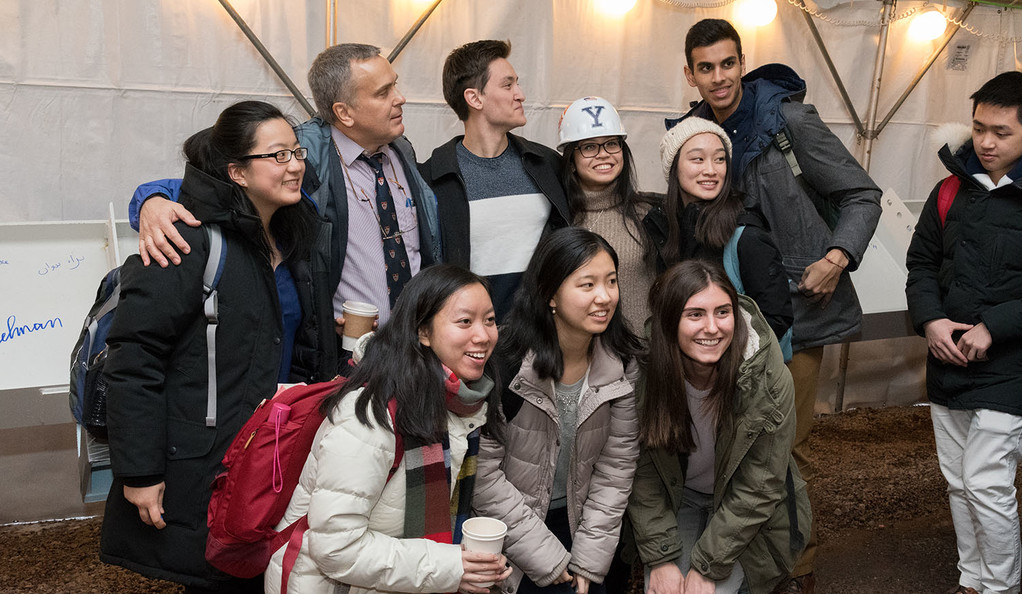 A group of Yale students pose with a painted girder at a ceremony for the new science building.