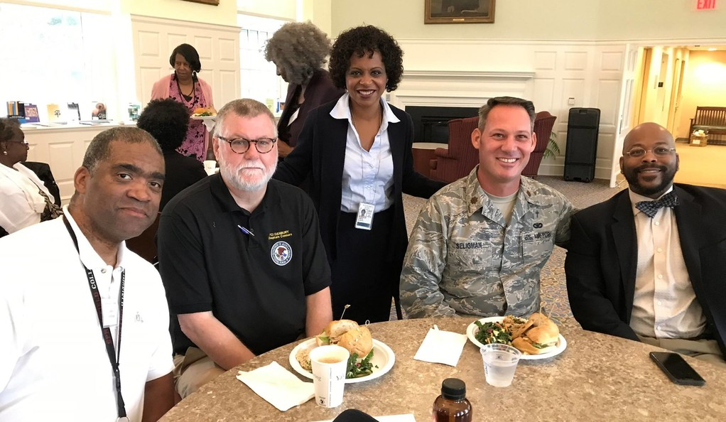 Five people posing for a photo at a luncheon event.