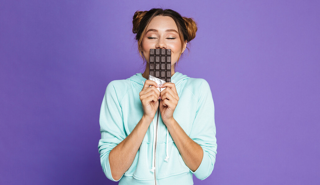 A woman smelling a chocolate bar.