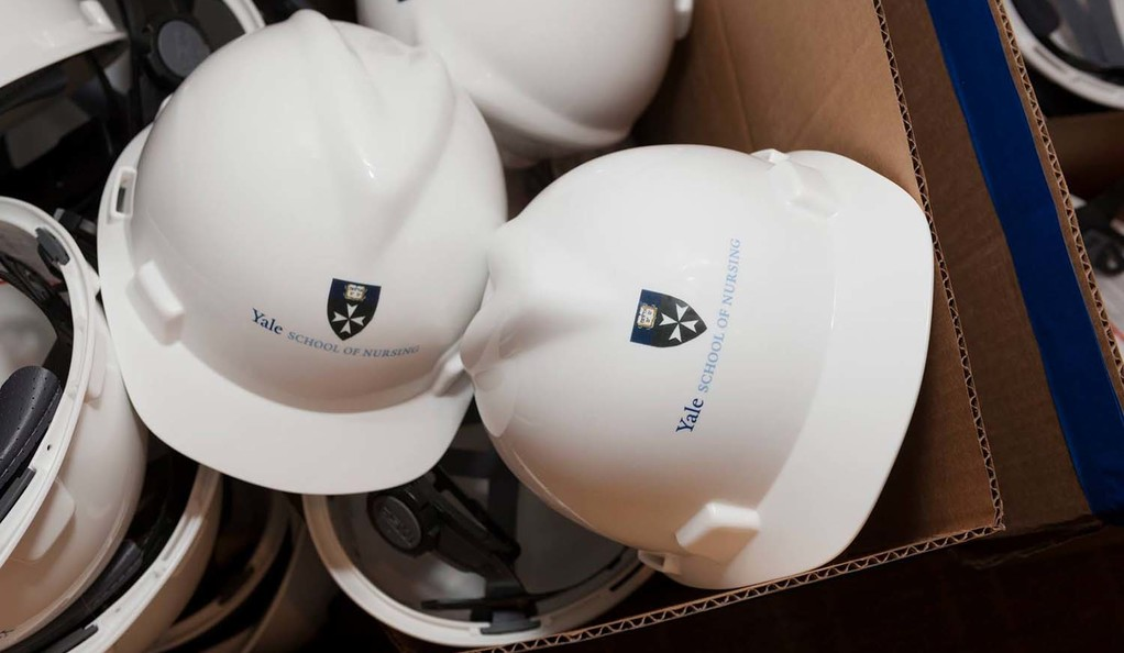 A closeup of a box of white hardhats with the Yale School of Nursing logo.