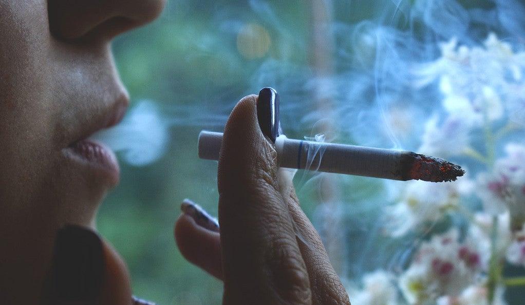 A closeup of a woman smoking a cigarette.