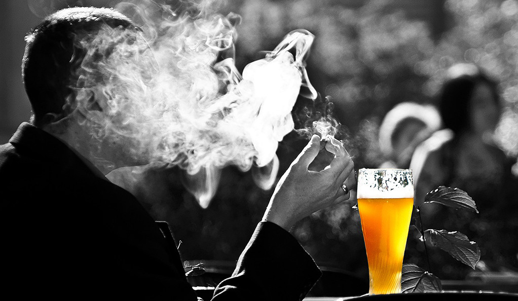 A black and white photo of a man smoking a cigarette, with a glass of beer highlighted in color.